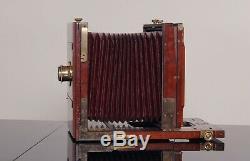 Ancien appareil photo à soufflet rouge en bois dacajou